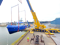 Ocean-going boat takes to the skies with crane lift launch